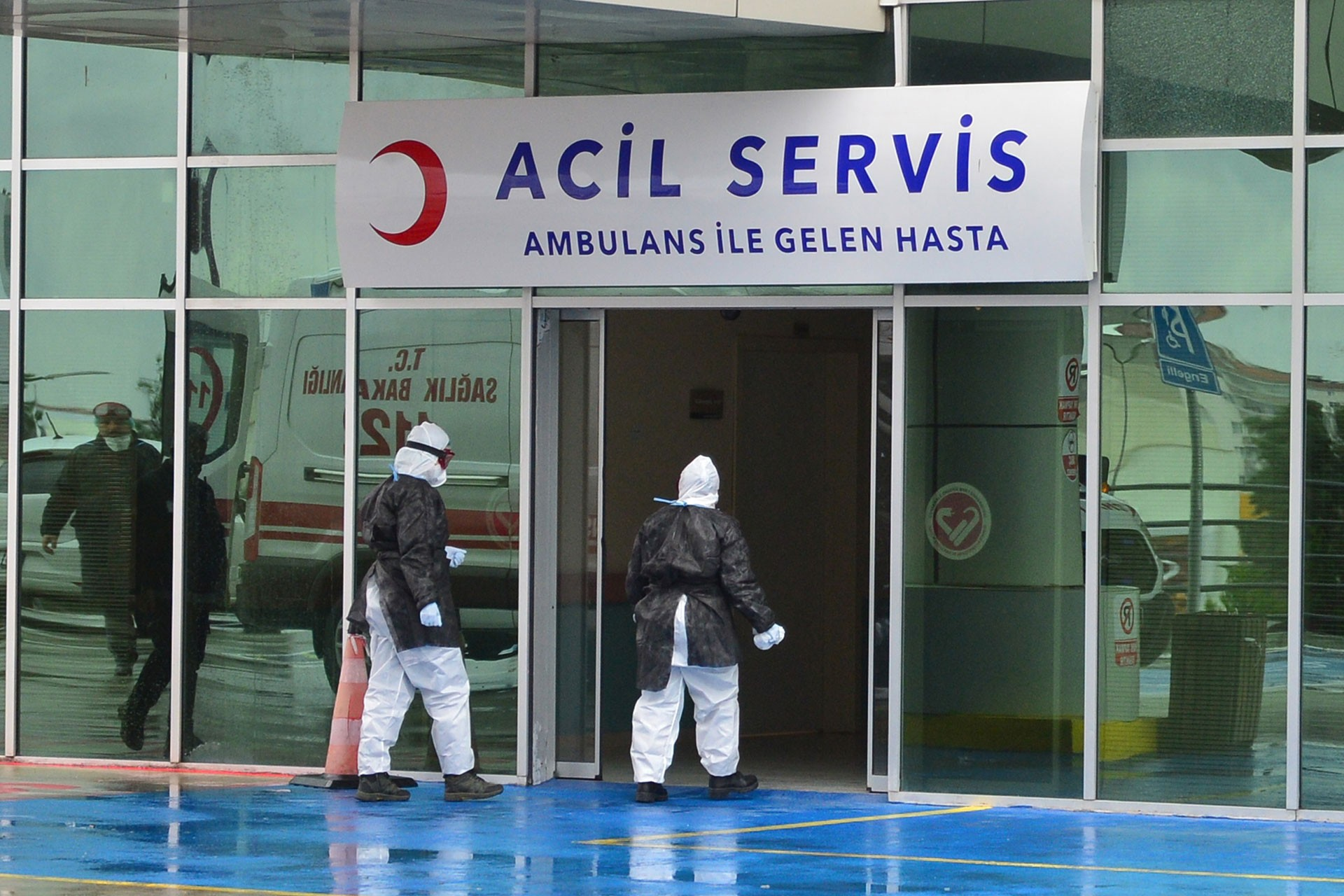 Hastane acil servisi kapısından giren iki sağlık çalışanı.
