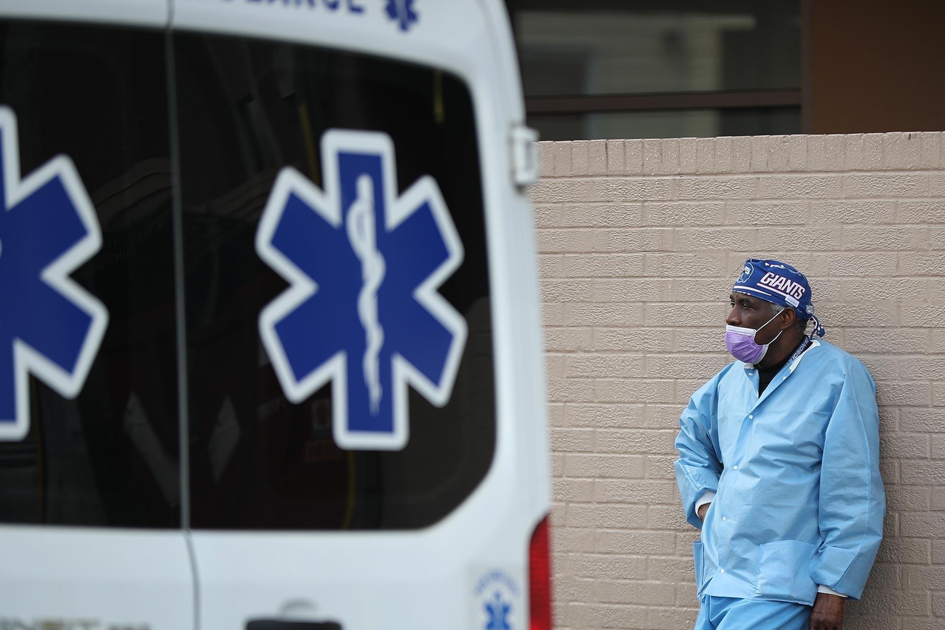 Ambulansın yanında duvara yaslanmış bekleyen orta yaşlı bir sağlık çalışanı.