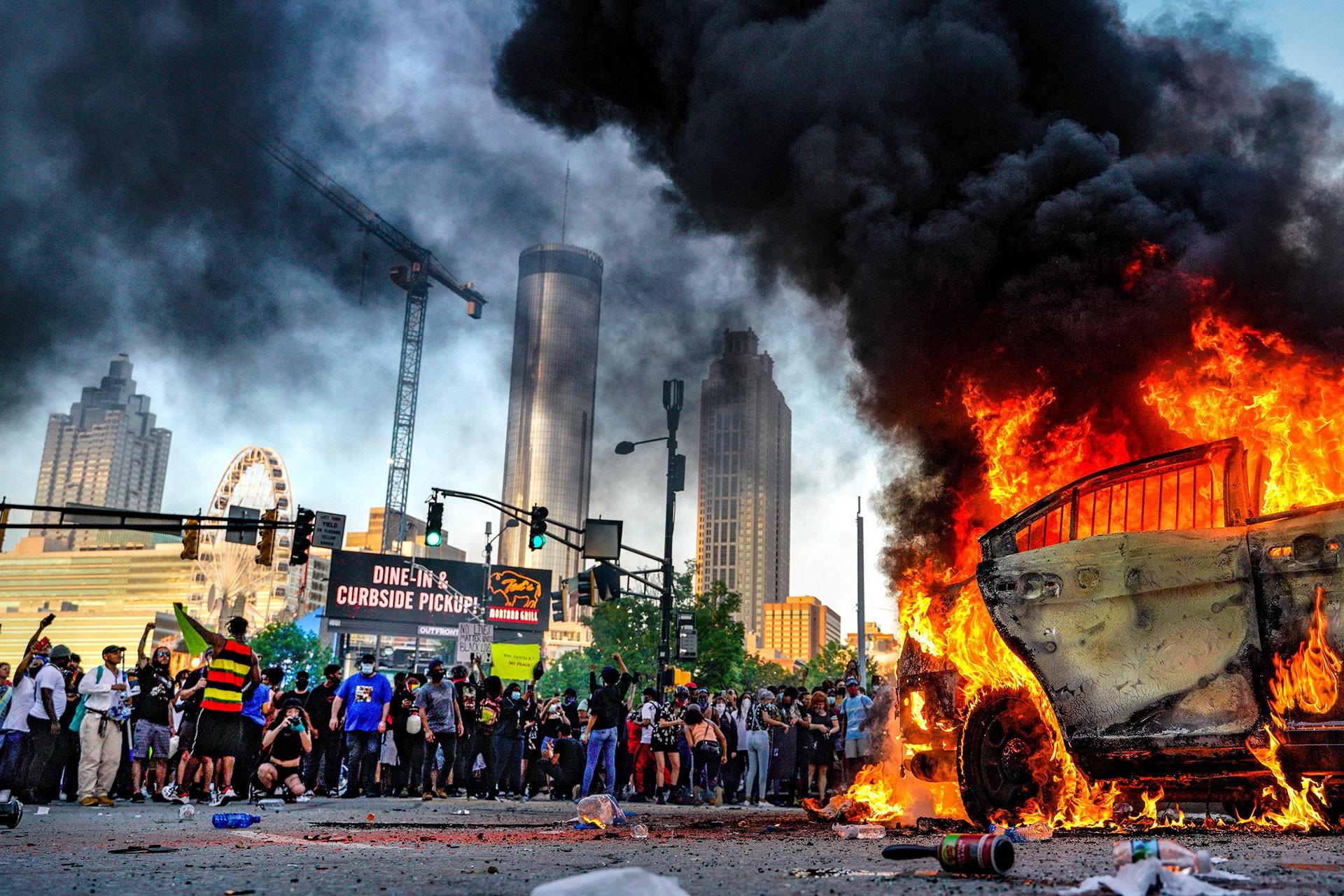 Çok sayıda kişi ırkçılığa karşı eylem yapıyor. Bir araç ateşe verilmiş.
