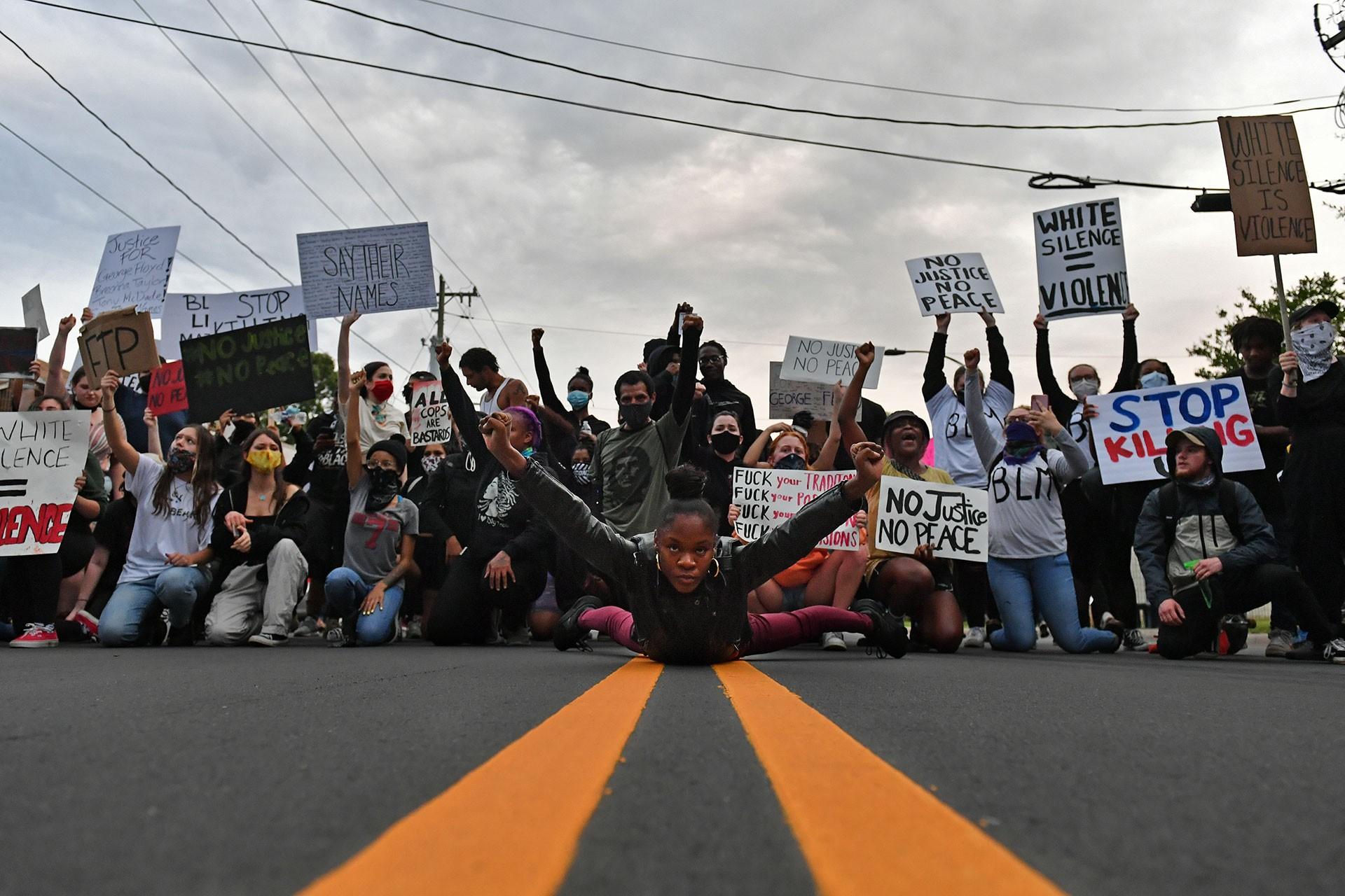 Çok sayıda kişi yere çökmüş ırkçılığa ve polis şiddetine karşı dövizler gösteriyor.