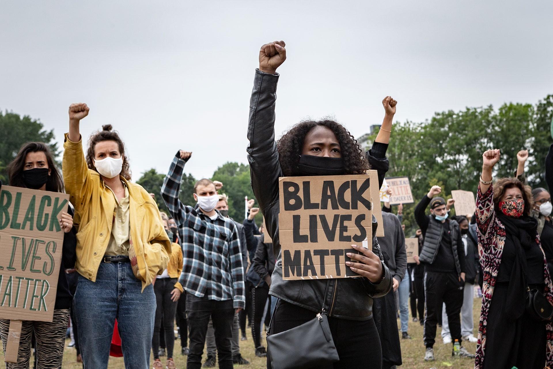 Siyahların yaşamı önemlidir yazılı döviz taşıyan genç kadın, sağ yumrupu havada