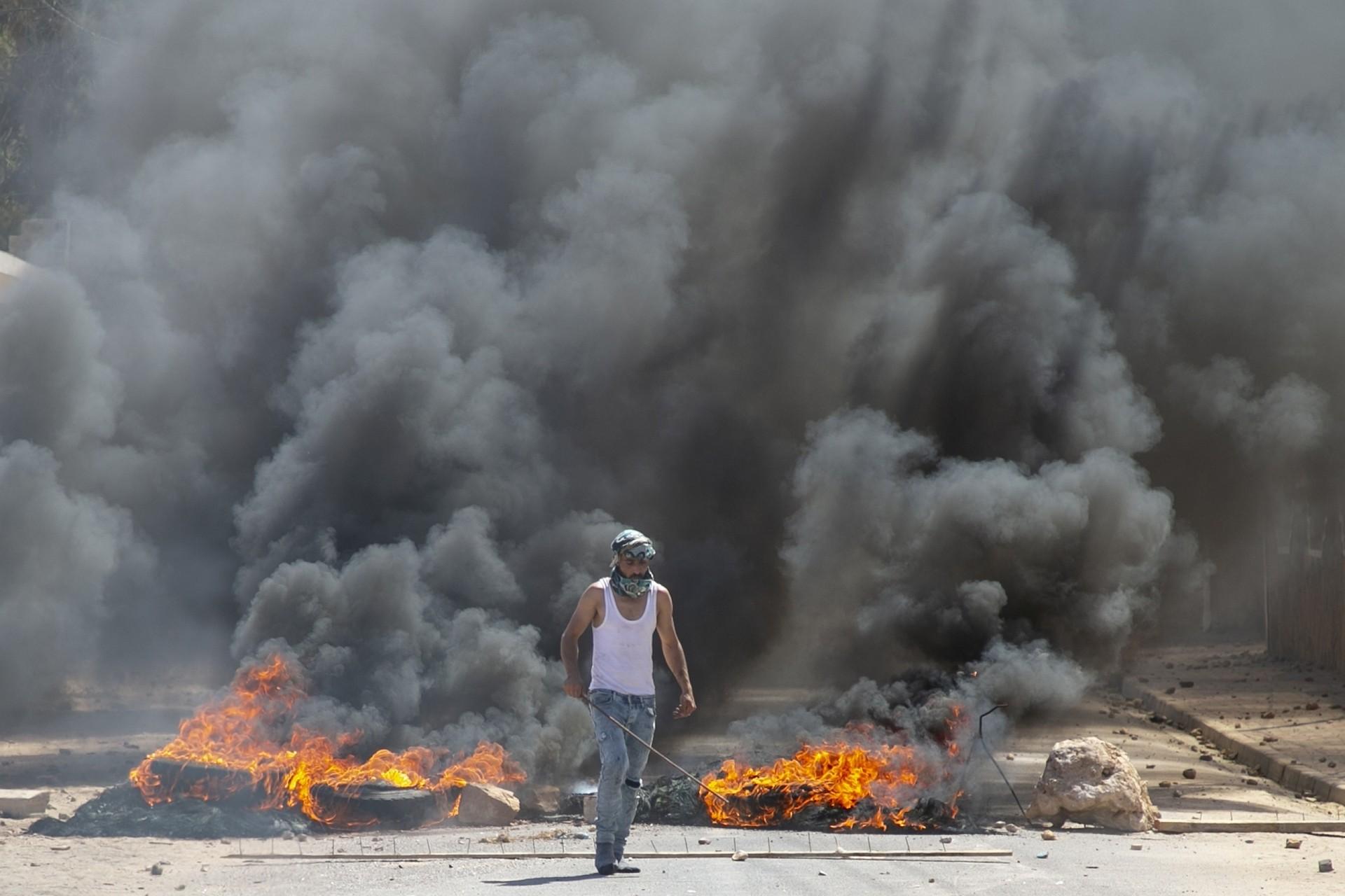 Tunus'ta bir genç sokakta yakılan ateşin önünde