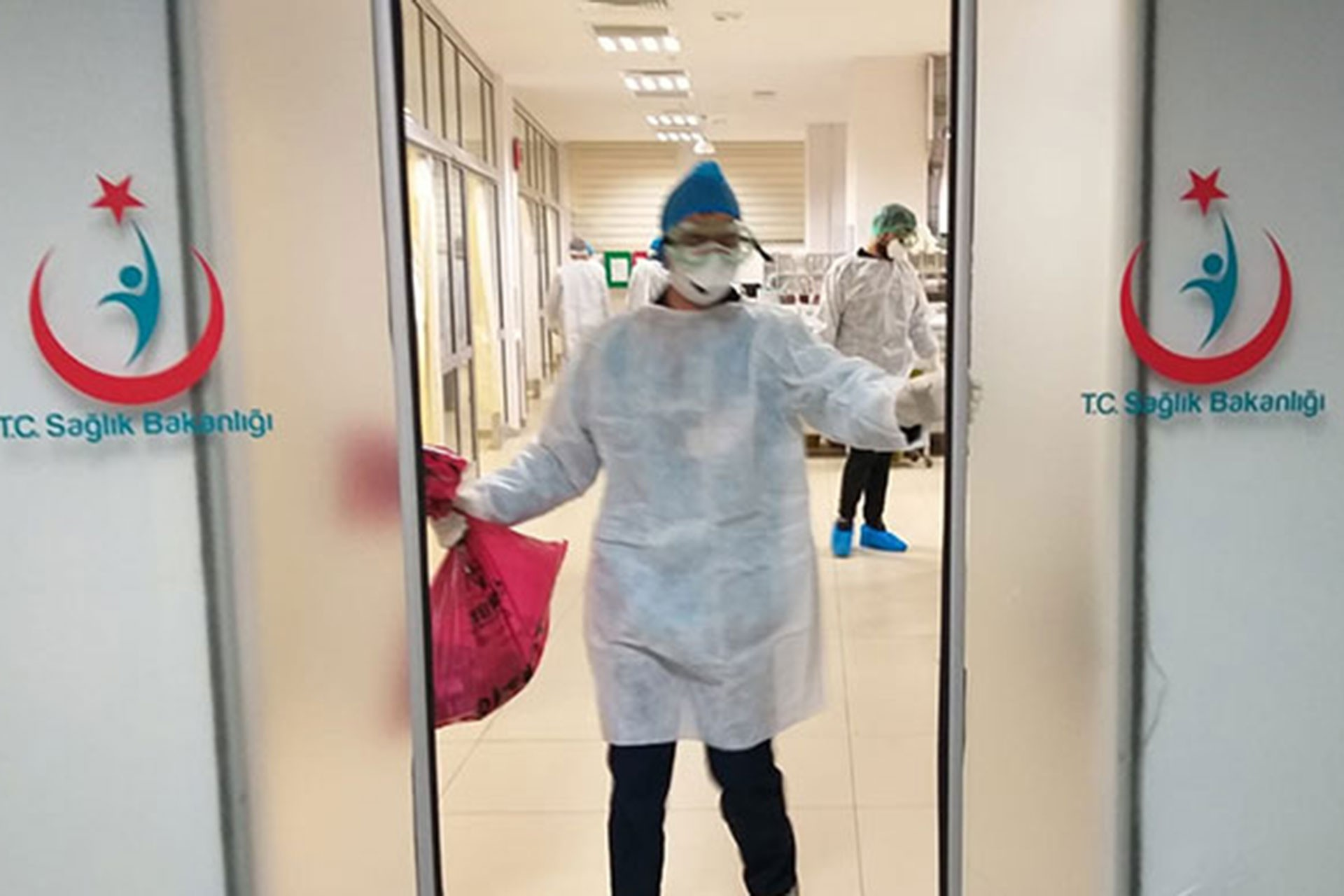 Sağlık Bakanlığı yazılı kapılar, koruyucu ekipmanları olan bir sağlıkçı