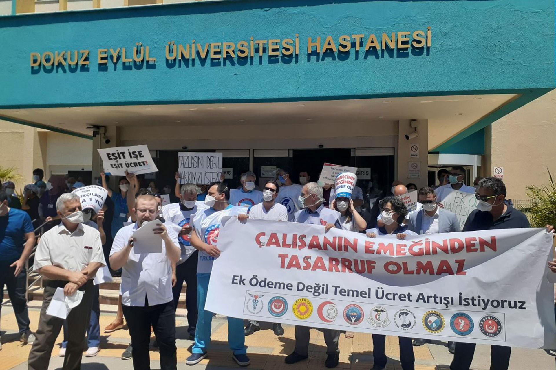 Dokuz Eylül Üniversitesi Hastanesi tabelası (yukarıda) önünde sağlık çalışanları basın açıklaması yapıyor
