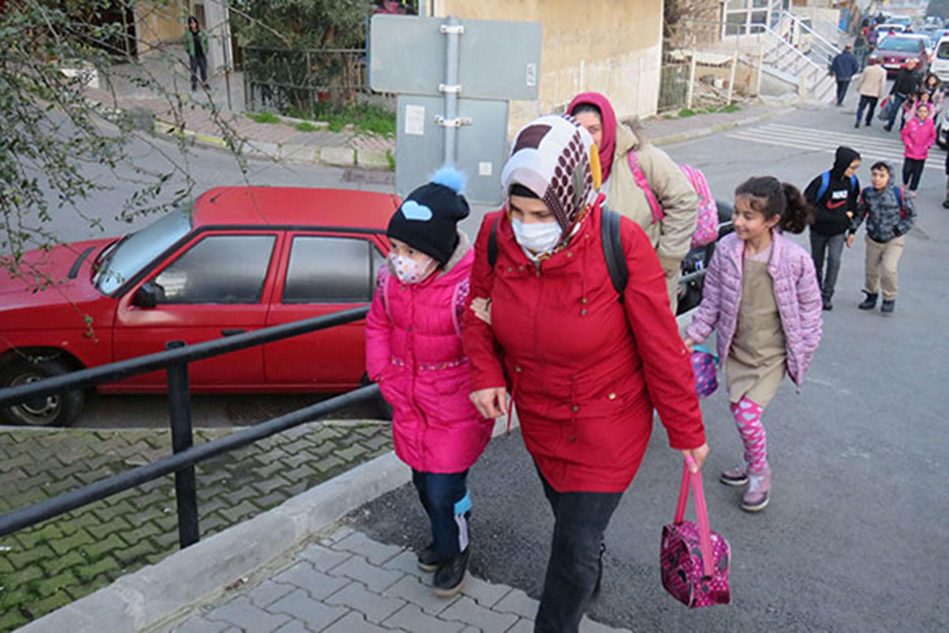Maskesi takılı çocuklar, ellerinden tutan anneleri ile yürüyor