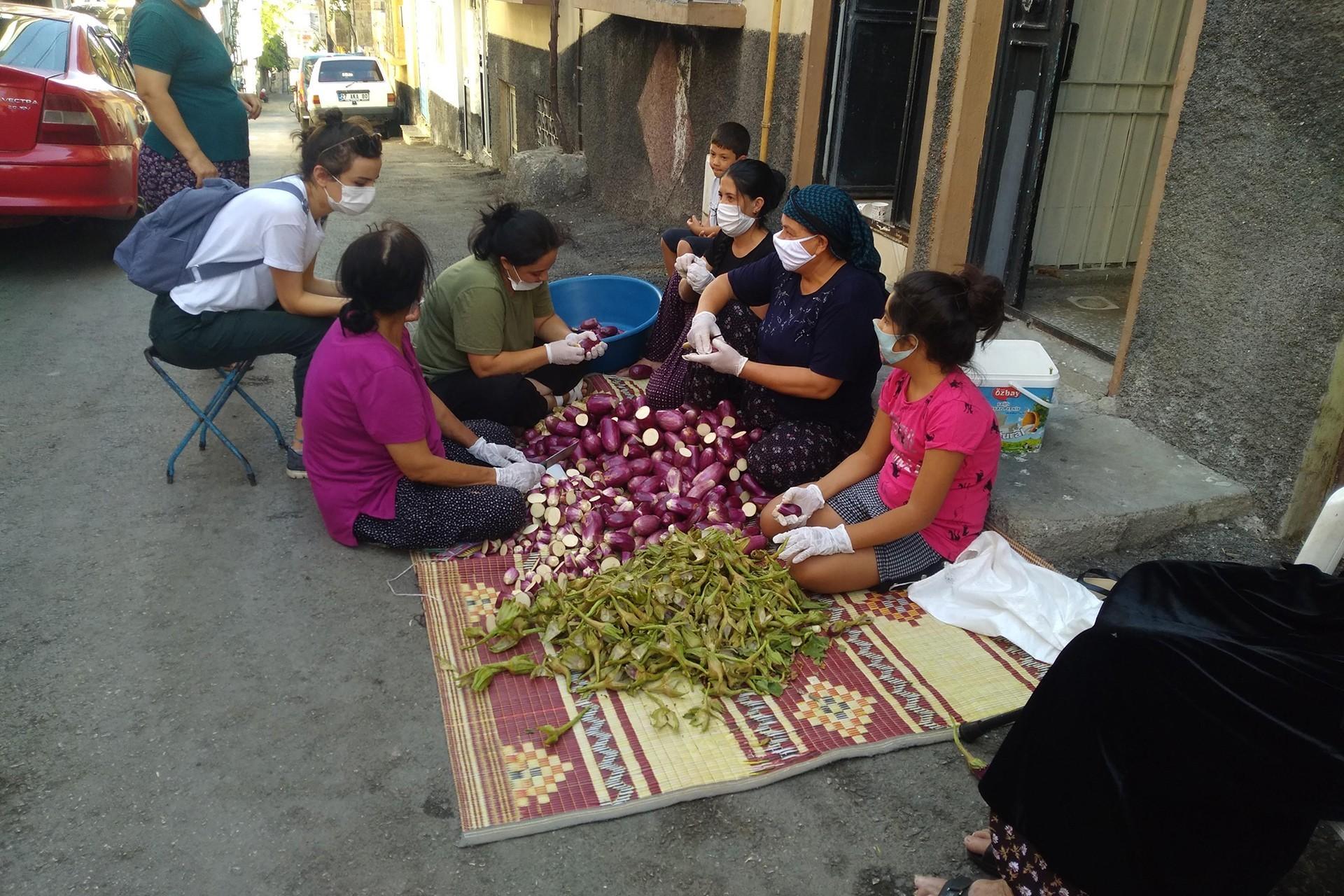 Sokakta patlıcan doğrayan kadınlar.
