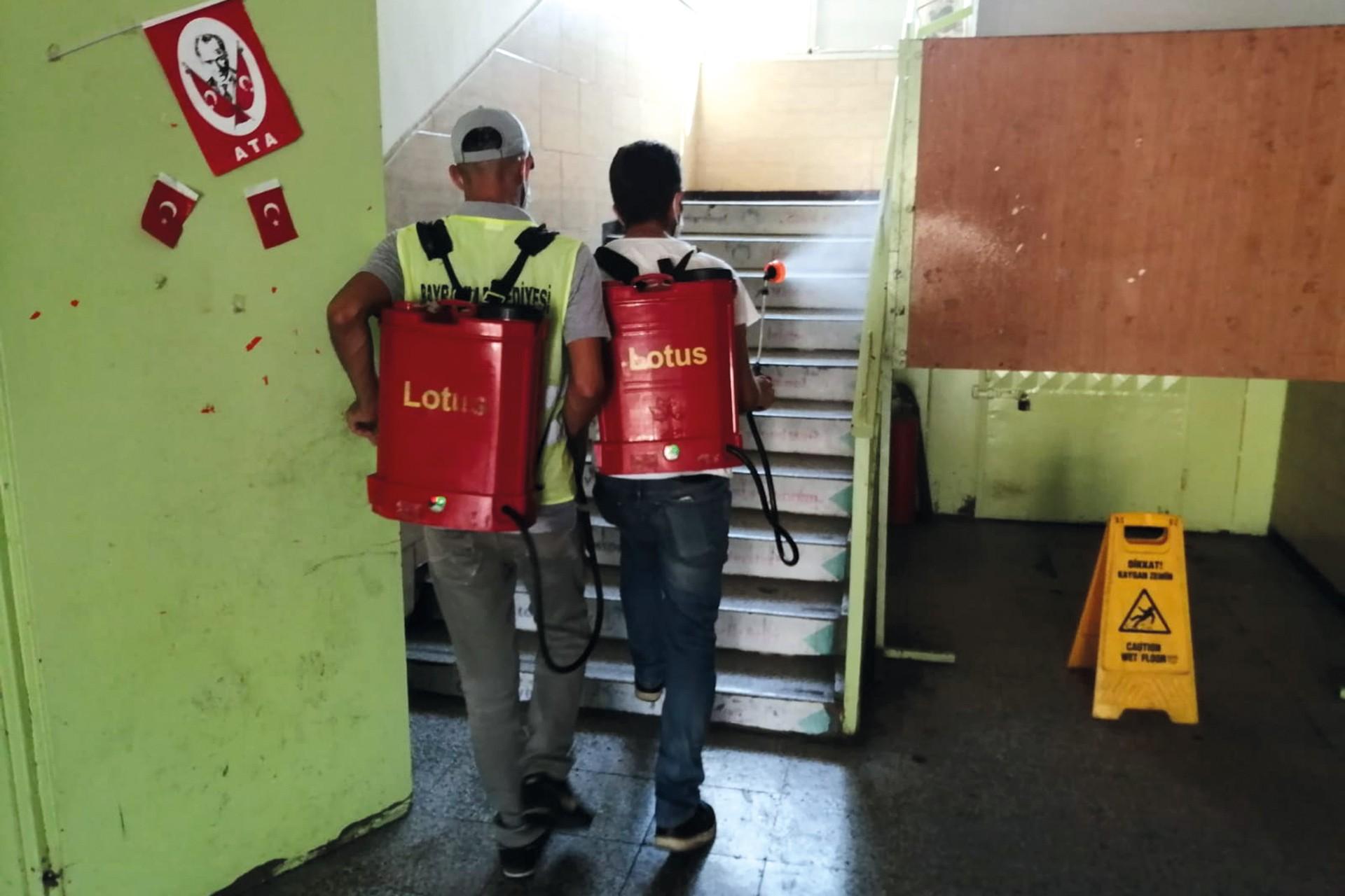 Okulu dezenfekte eden iki görevli