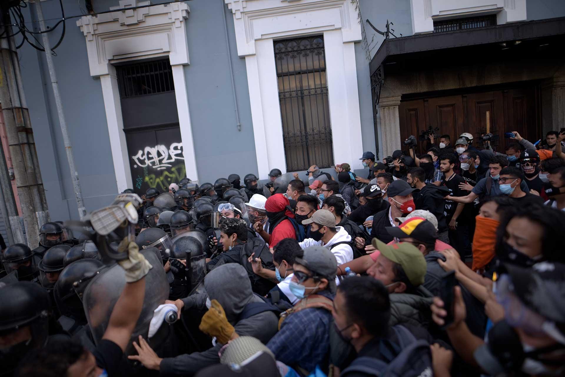 Guatemala'da protesto için kongre binasına girmek isteyenler (sağda) ve karşılarında polis