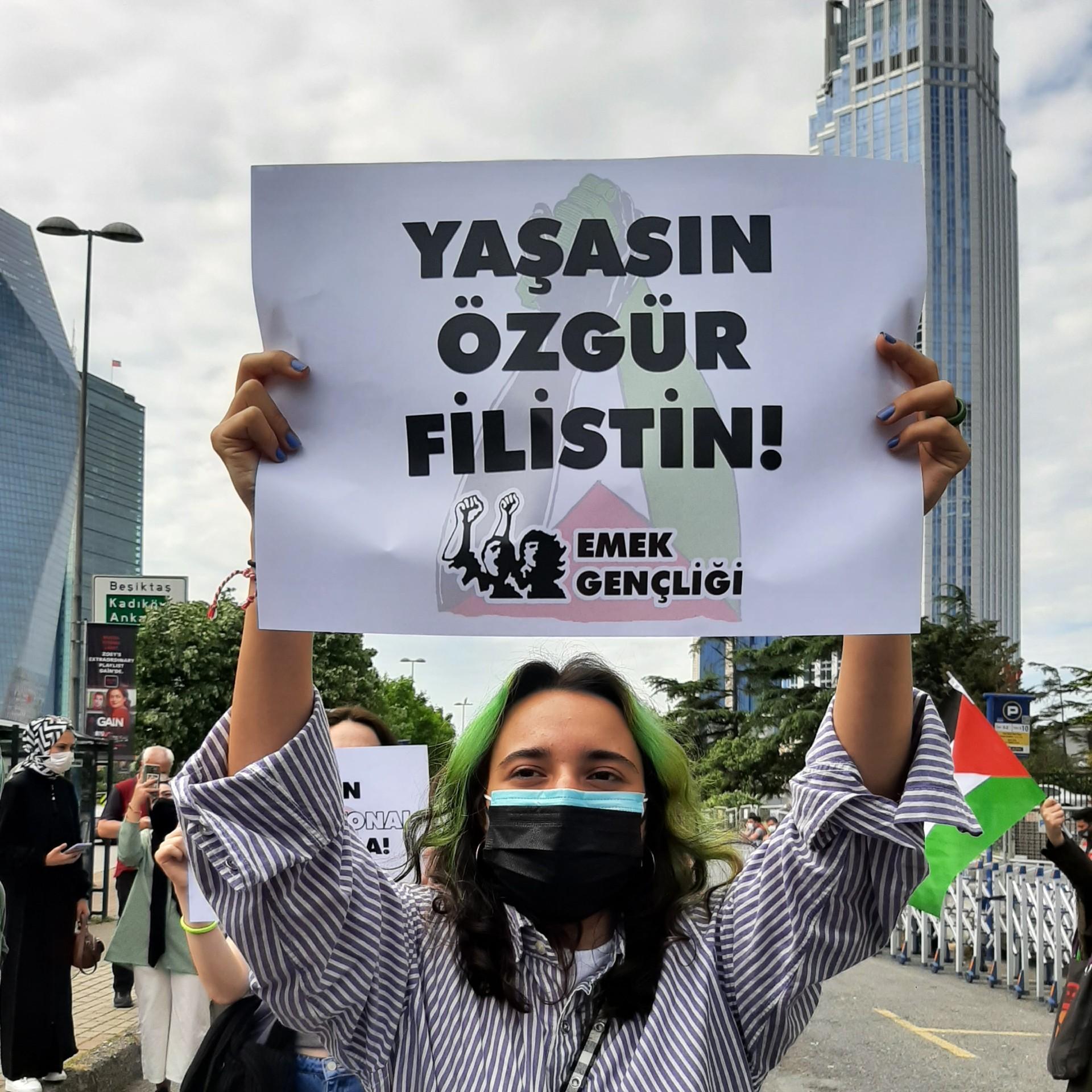 Emek Gençliği'nin İsrail Başkonsolosluğu önünde düzenlediği protesto eyleminde 'Yaşasın özgür Filistin' yazılı döviz tutan bir genç kadın.