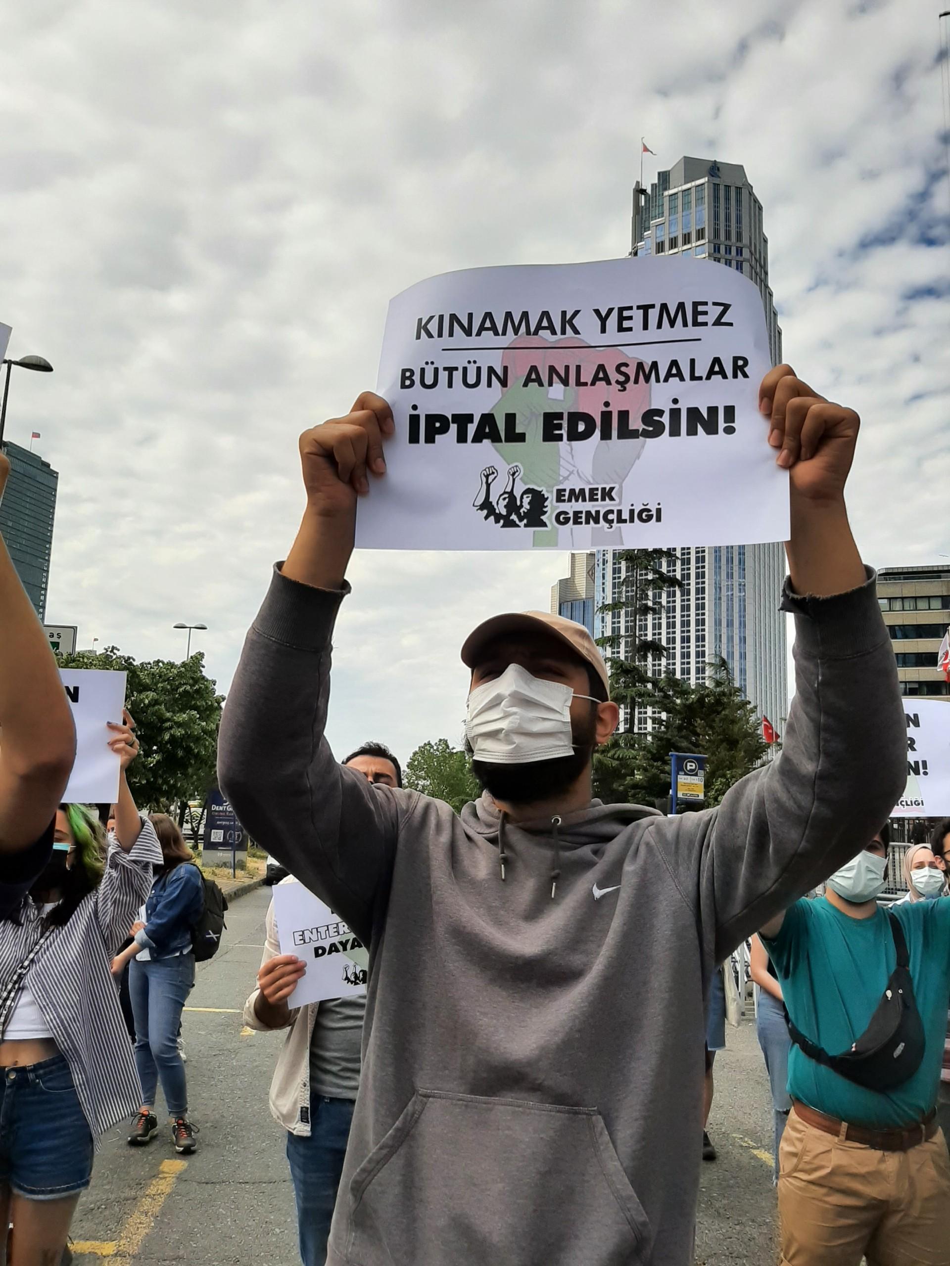 Emek Gençliği'nin İsrail Başkonsolosluğu önünde düzenlediği protesto eyleminde 'Kınamak yetmez, bütün anlaşmalar iptal edilsin!' yazılı döviz tutan bir genç.