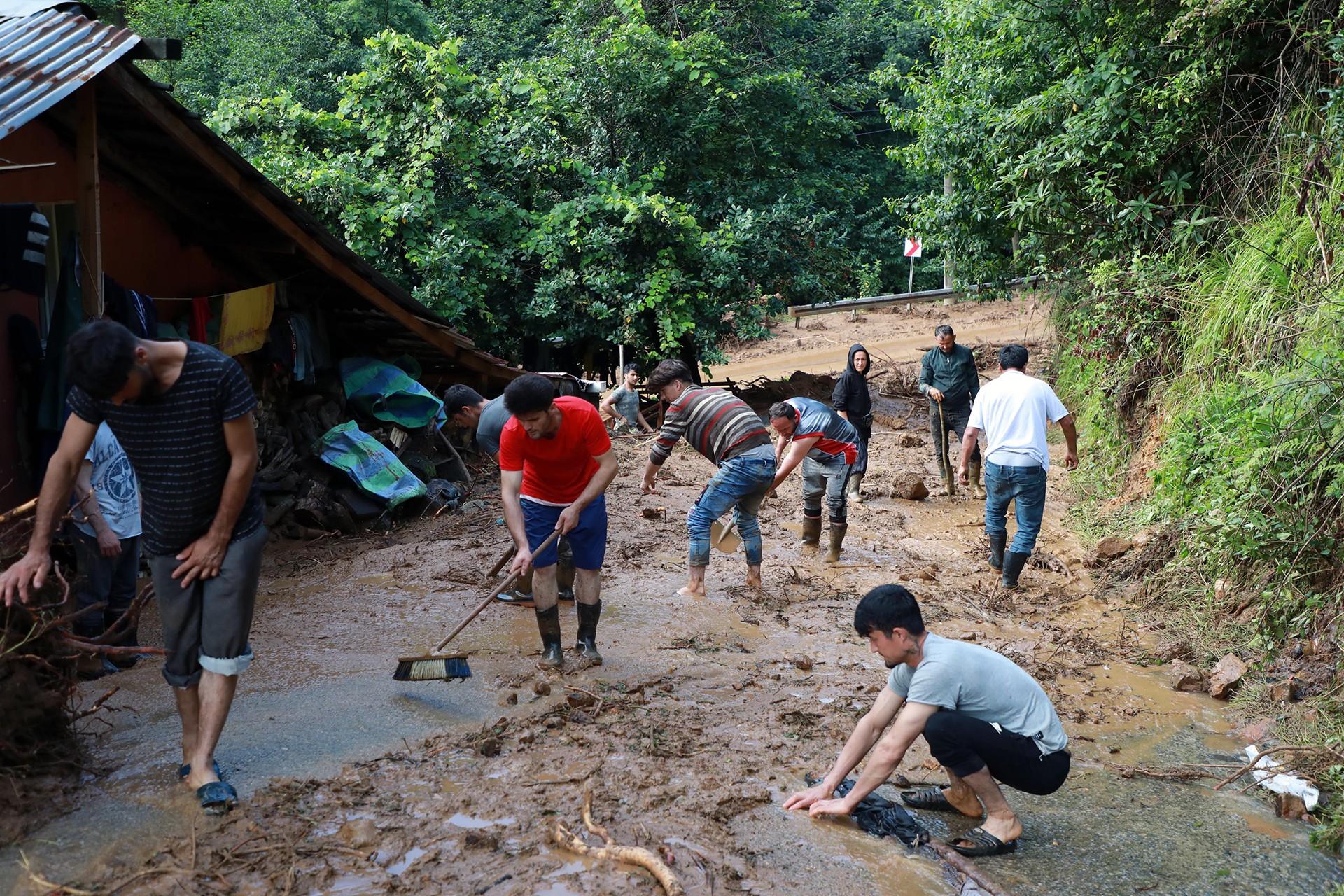 Rize'de yaşanan sel felaketinde sokaktaki çamuru temizlemeye çalışan insanlar.