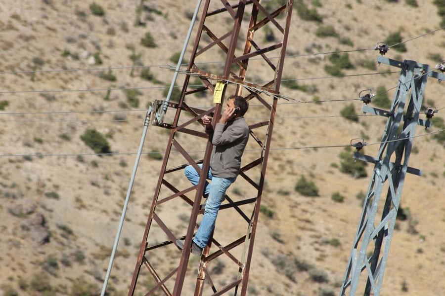 Telefonla konuşmak için elektrik direğine çıkıyorlar