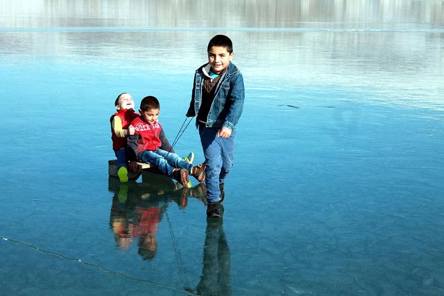 Buz tutan Çıldır Gölü'nde 'aşık' oynayıp, kızakla kaydılar