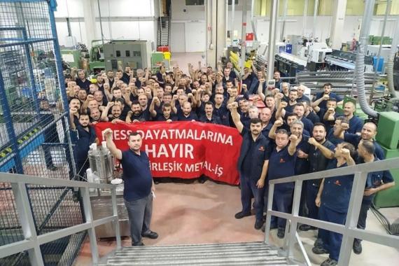Fabrikada toplanan metal işçilerinin yumrukları havada, ellerinde büyük kırmızı bir pankart var. Pankartta, MESS dayatmalarına hayır, Birleşik Metal-İş yazıyor.