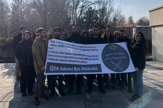 Ankara'da KYK Genel Müdürlüğü binası önünde açıklama yapan üniversite öğrencileri, 'Eğitim hakkımız, burs ihtiyacımız!' yazılı pankartı tutarken