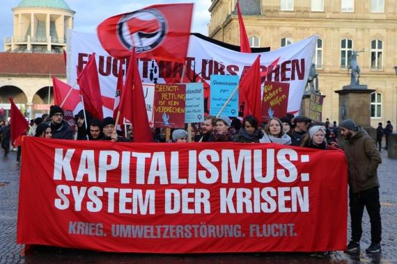 Almanya Stuttgart'ta mülteci haklarının korunması için yapılan eylemde 'Kapitalizm: Kriz sistemi' yazılı pankart ve arkasında duranlar