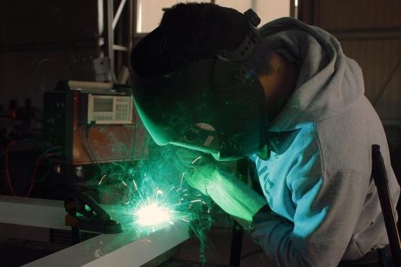 Metal işçisi yüzünde maske ile kaynak yaparken