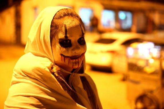 Bocuk gecesi etkinliği için yüzünü boyamış ve üzerine beyaz çarşaf örtmüş bir genç