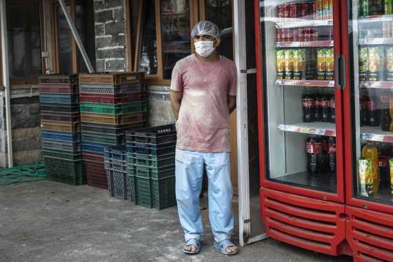 İstanbul\'da koronavirüs (Kovid-19) salgını dolayısıyla alınan önlemler sonrası yüzünde maske ve kafasında bone ile dükkanın önünde duran fırıncı.