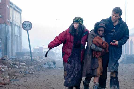 Children of Men filminden bir kare, yıkık dökük bir sokak, bir kadın etrafa bakıyor, yanında bir kız çocuğu ve erkek