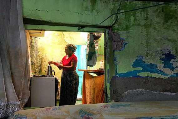 duvarlarının sıvası dökülmüş bir odanın içinde ocak üstünde çay demleyen kadın