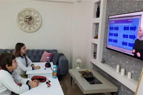 evde televizyondan EBA TV'yi izleyen iki çocuk