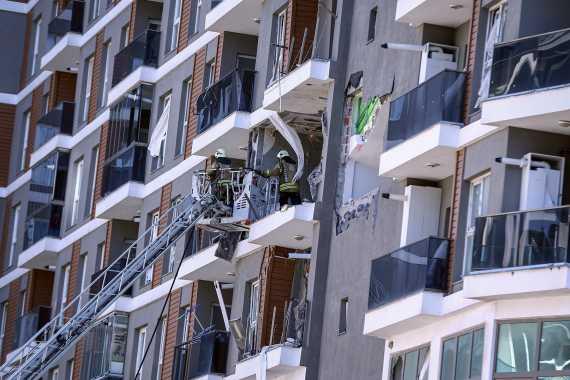 İki itfaiye çalışanı merdivende, patlamanın olduğu bina ve yıkık dökük pencereler