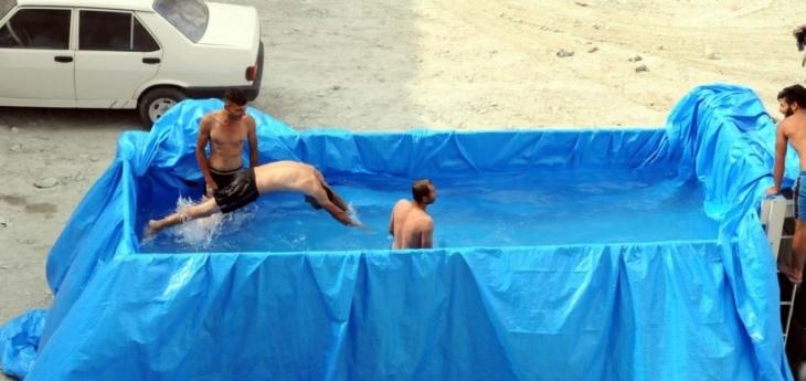 Sıcaktan bunalan inşaat işçileri kamyon kasasını havuza çevirdi
